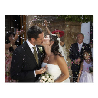 Guests throwing confetti over kissing bride and postcard
