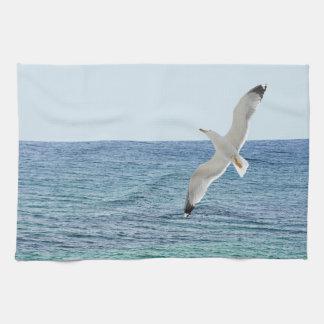Gull flying above a sea tea towel