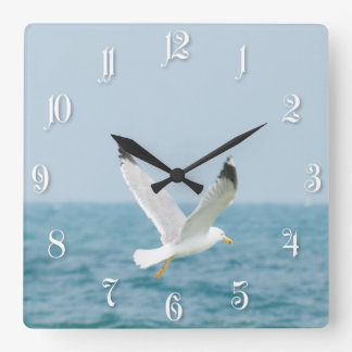 Gull flying above sea square wall clock