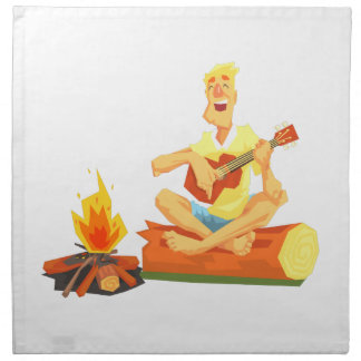 Guy Playing Guitar Sitting On A Log Next Napkin
