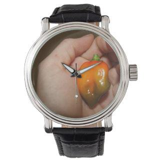 Habanero hot pepper in female hand wrist watch