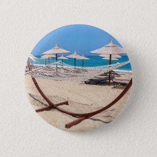 Hammock with beach umbrellas at coast 6 cm round badge