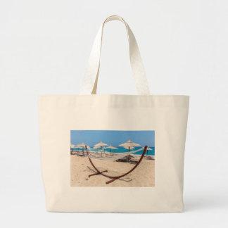Hammock with beach umbrellas at coast large tote bag