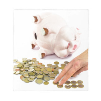 Hand counting euro coins from piggy bank notepad