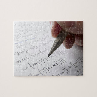 Hand doing math homework puzzle