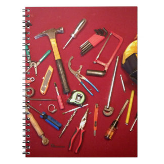 Hand held tools and tool bag red background notebook