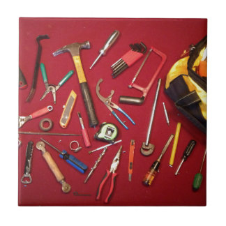 Hand held tools and tool bag red background small square tile
