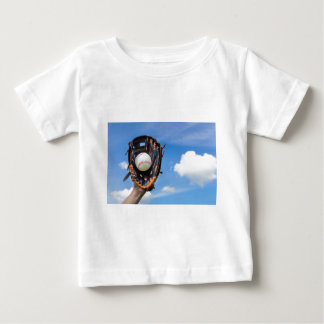 Hand holding baseball in glove with blue sky baby T-Shirt