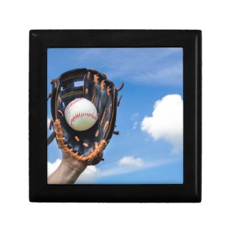 Hand holding baseball in glove with blue sky gift box