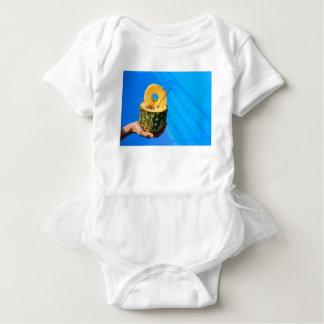 Hand holding fresh pineapple above swimming pool baby bodysuit