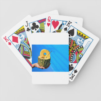 Hand holding fresh pineapple above swimming pool bicycle playing cards