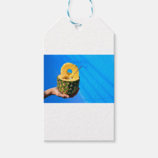 Hand holding fresh pineapple above swimming pool gift tags