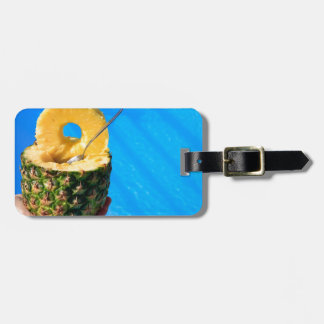 Hand holding fresh pineapple above swimming pool luggage tag