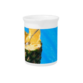 Hand holding fresh pineapple above swimming pool pitcher