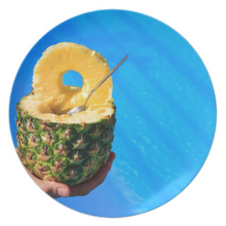 Hand holding fresh pineapple above swimming pool plate