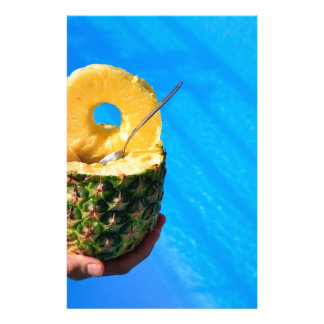 Hand holding fresh pineapple above swimming pool stationery