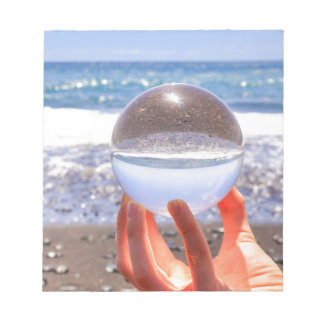 Hand holding glass sphere at beach and sea notepad
