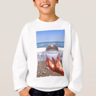 Hand holding glass sphere at beach and sea sweatshirt