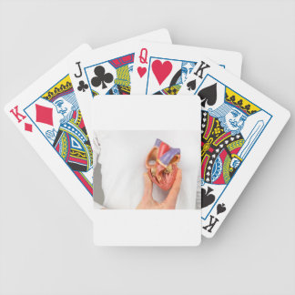 Hand holding heart model in front of chest poker deck