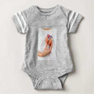 Hand holding model heart on chest baby bodysuit