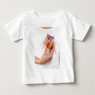 Hand holding model heart on chest baby T-Shirt
