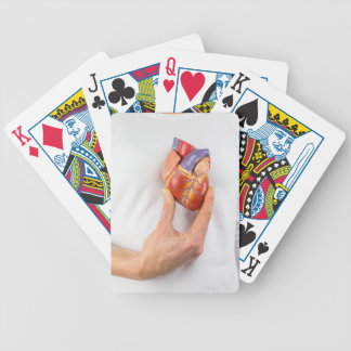 Hand holding model heart on chest bicycle playing cards
