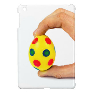 Hand holding painted yellow easter egg with dots cover for the iPad mini
