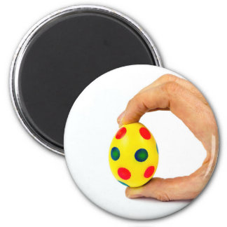 Hand holding painted yellow easter egg with dots magnet