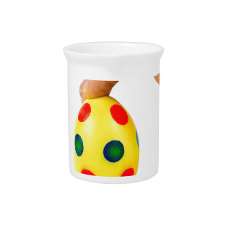 Hand holding painted yellow easter egg with dots pitcher