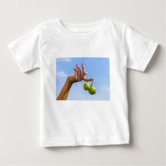 Hand holding two hanging green pears in blue sky baby T-Shirt