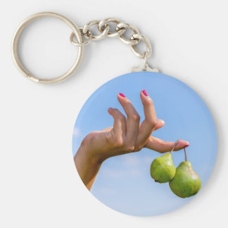 Hand holding two hanging green pears in blue sky key ring
