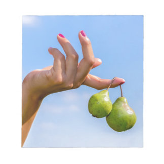 Hand holding two hanging green pears in blue sky notepad