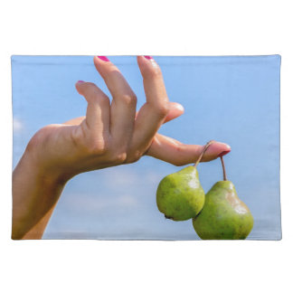 Hand holding two hanging green pears in blue sky placemat