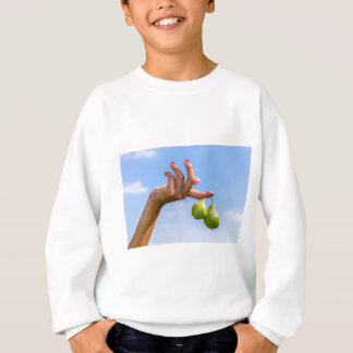 Hand holding two hanging green pears in blue sky sweatshirt