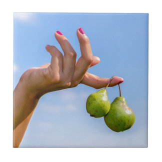 Hand holding two hanging green pears in blue sky tile
