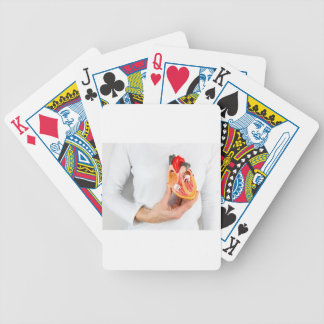 Hand holds human heart model at body bicycle playing cards