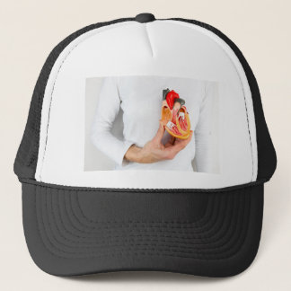 Hand holds human heart model at body trucker hat
