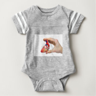 Hand holds model human heart between fingers baby bodysuit