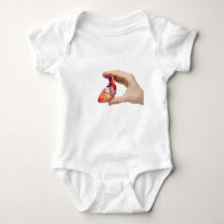 Hand holds model human heart between fingers baby bodysuit