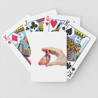 Hand holds model human heart between fingers bicycle playing cards