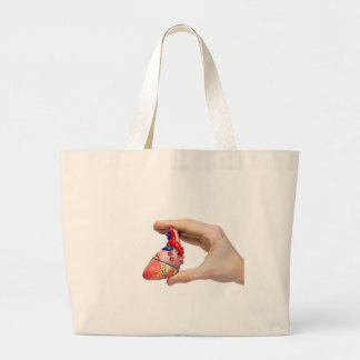 Hand holds model human heart between fingers large tote bag