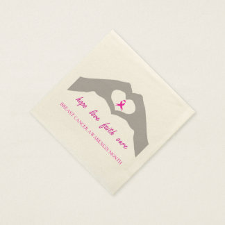 Hand making heart sign with breast cancer ribbon paper napkins