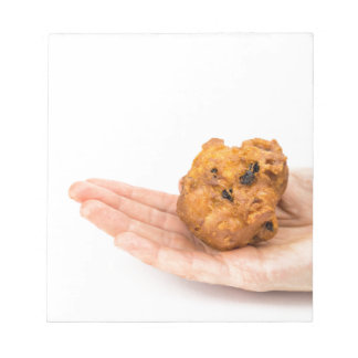 Hand palm showing fritter or oliebol notepad