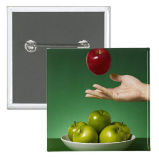 hand tossing red apple in the air and green 15 cm square badge