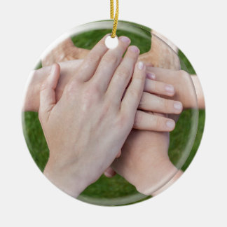 Hands arms uniting in glass sphere ceramic ornament