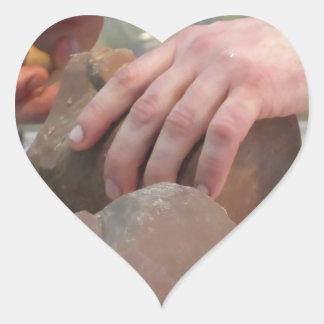 Hands cut out a sculpture from a chocolate heart sticker