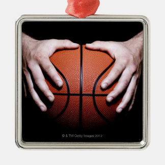 Hands holding a basketball metal ornament