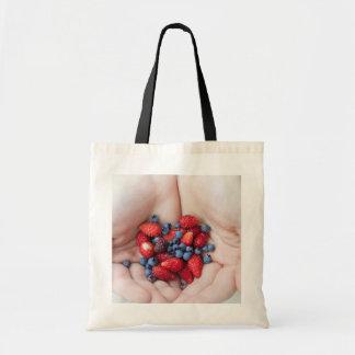 Hands holding berries bags