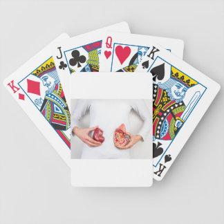 Hands holding model of human kidney organ at body. poker deck