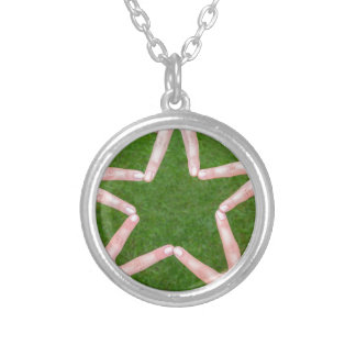 Hands of girls making star shape above grass round pendant necklace